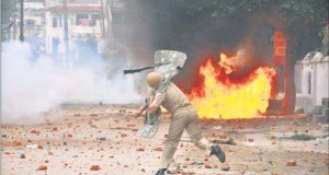 A policeman lobs a teargas shell at rioters (unseen) in Saharanpur on Saturday.
