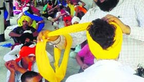 Tejinder Singh ties turban on a volunteer at a gurdwara in Mansa.