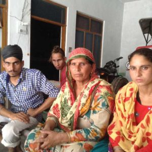 """Sukhwant Kaur, whose brothers-in-law were among 28 beaten up in jail, with family. One died, other was injured and shifted to Amritsar after release; her husband died of heart attack, """"pained by all this""""."""